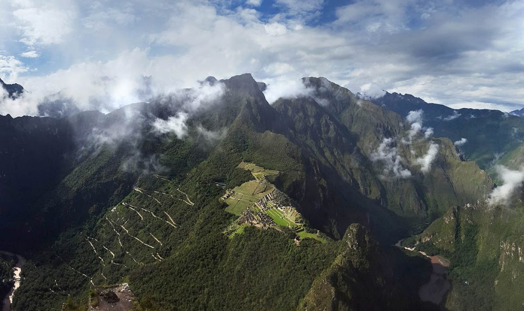 The view looking out from Huayna Picchu peak. The surrounding mountains and river below are visible. The weather is partly cloudy.