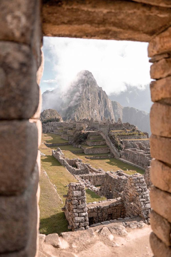A view looking through the main ruins of Huayna Picchu mountain covered in fog. The sun is bright and illuminating the ruins.