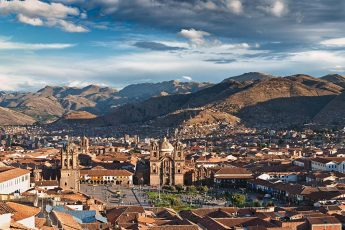 View of the historic center of Cusco with the Plaza de Armas and Cusco Cathedral. The Andes mountain loom in the background.