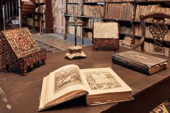 An antique book sits open on a wooden table with more old books in the bookcase behind