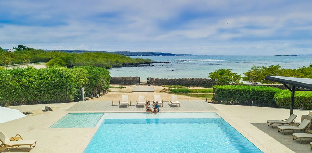 A high angled view of a couple sitting at Finch Bay's rectangular pool and square jacuzzi with beige lounge chairs on all sides. In the background, a walkway leads to a beach and rocky ocean cove.