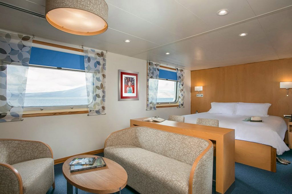The Darwin Suite on the Galapagos cruise ship Santa Cruz II has blue floors and curtains, white linens, a beige sitting area, and warm wood finishings. Two large windows look out on the sea.