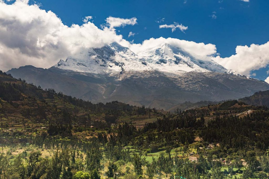 White clouds wrap around Peru's snow-capped Huascaran Peak with a green valley filled with trees in the foreground.