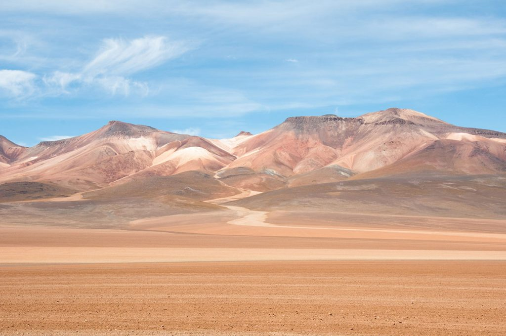 The tan and orange colors of the Atacama desert sand stand in contrast to the blue of the sky. The mountains are located in the distance.