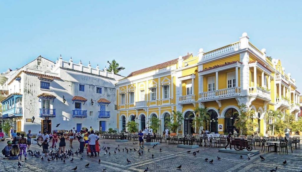 A bright yellow building shines in the sun while tourists take photos amid a massive gathering of pigeons in Cartagena.