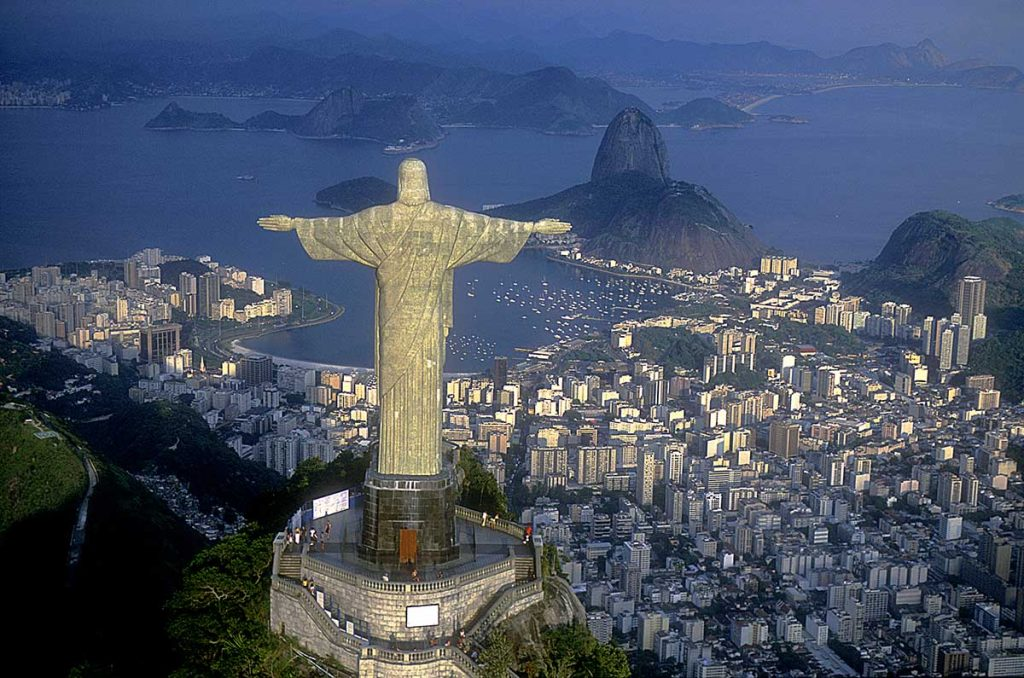 The sun illuminates one side of the Christ the Redeemer statue. The statue is pictured overlooking the city of Rio.