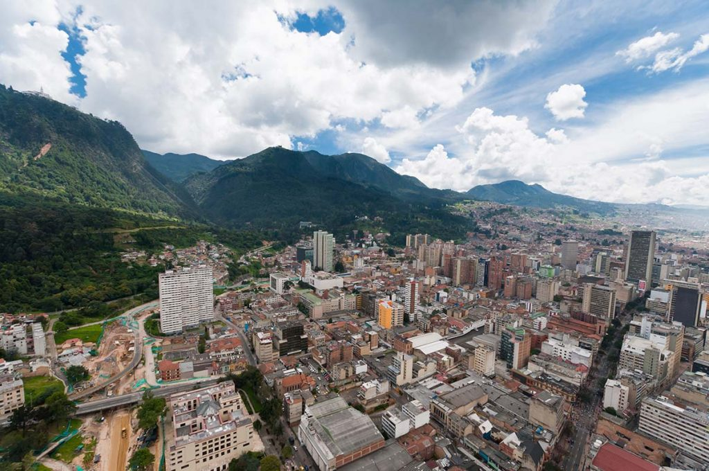A photo taken from above the city of Bogotá, Colombia looking down on the buildings and mountains.