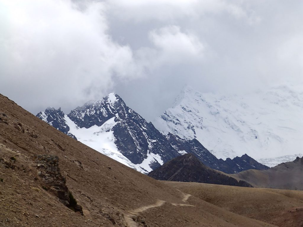 A road leading down a dirt mountain and snowy peaks in the background on the Ausangate trek