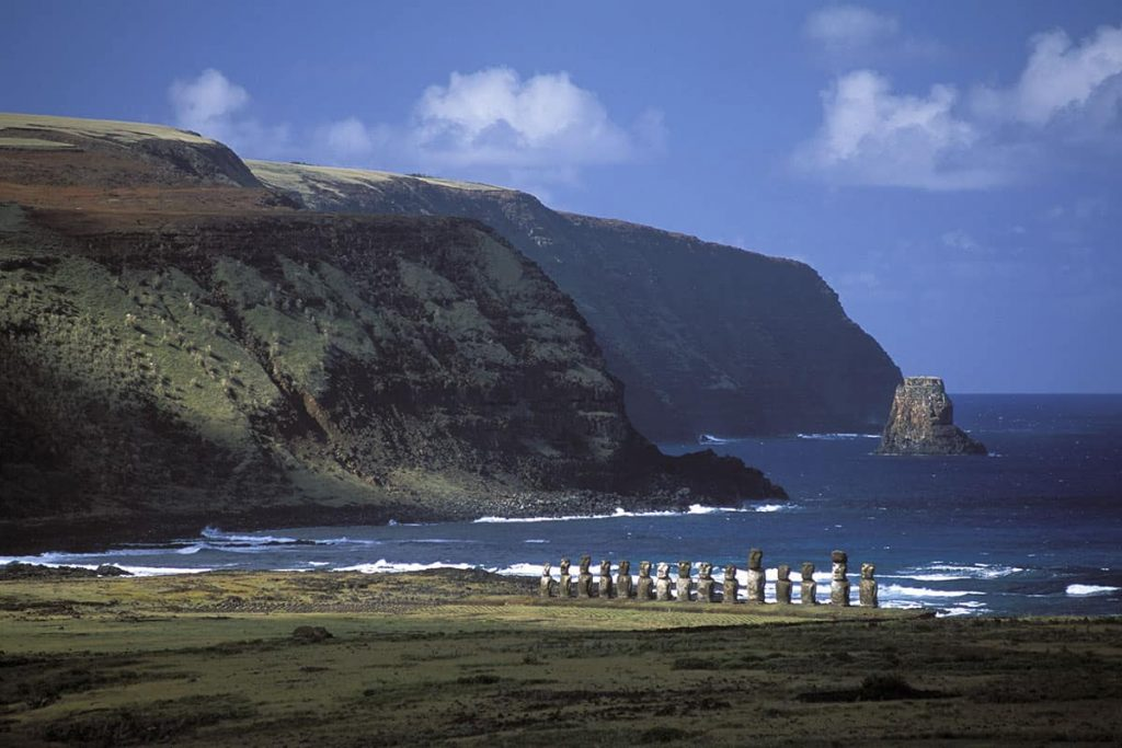 A bit of light shines on the mysterious carved statues of Easter Island. They are lined up in a row and situated on the coastline.