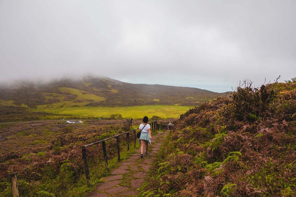 A woman walks along a stone path on San Cristobal Island with drizzly weather.