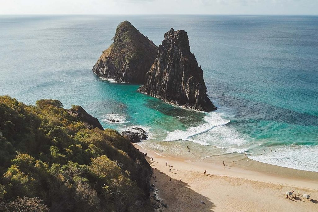 A view looking down on the pristine beaches of Fernando de Noronha in Brazil. Two large rocks stand out in the blue-green waters of the ocean.