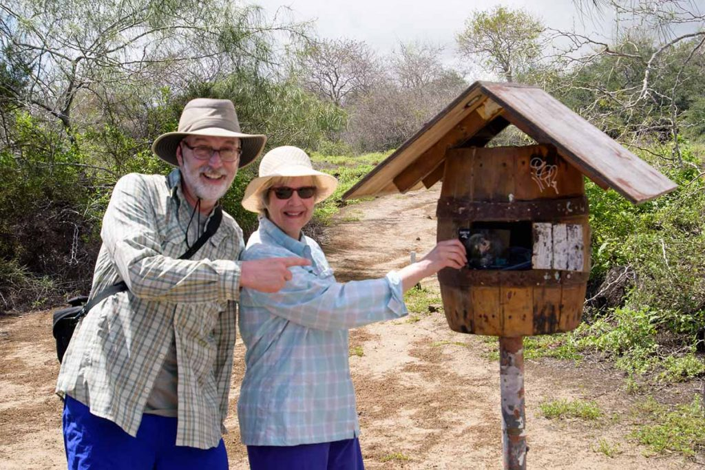 A couple poses as they leave a postcard in a raised barrel that serves as a post office box at Post Office Bay on Floreana Island.