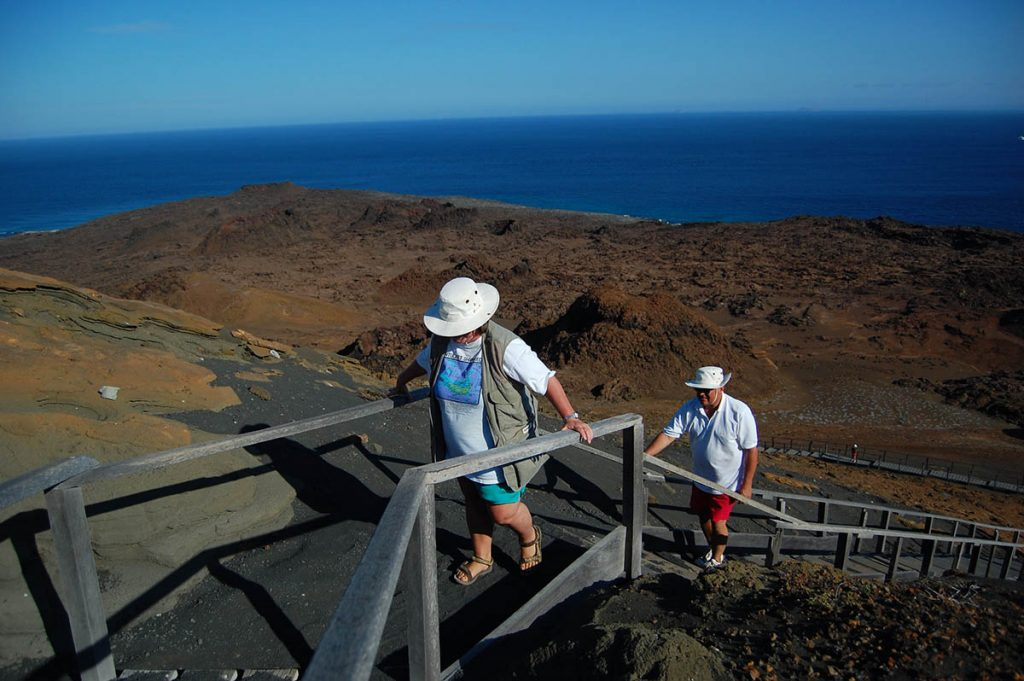 Travelers use a wooden railing as they hike up a steep hill on Bartolomé Island with a dry landscape and open sea below.