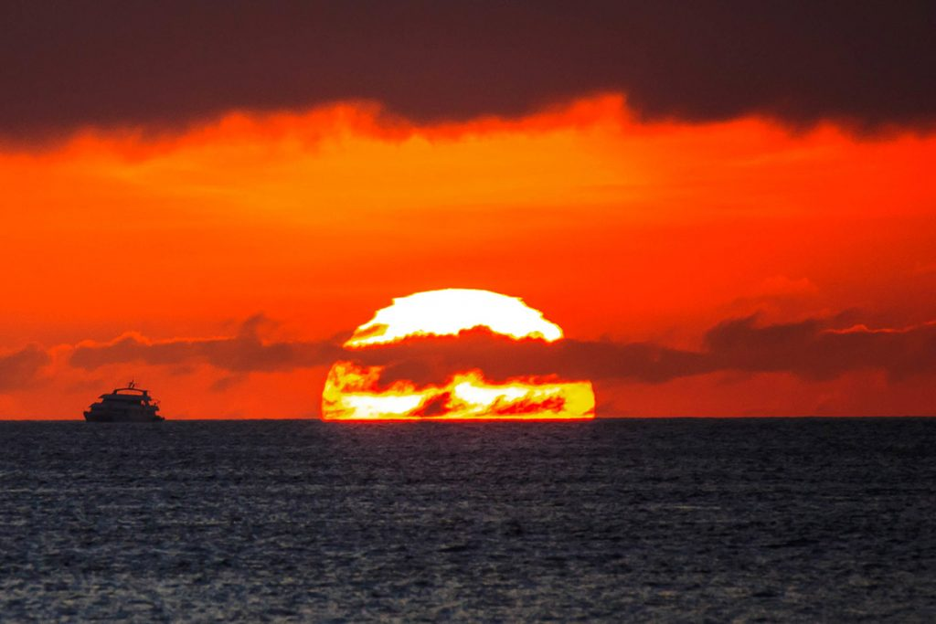 A cruise ship sits on the ocean horizon to the left of the immense setting sun. The sky turns red with smoky purple clouds.