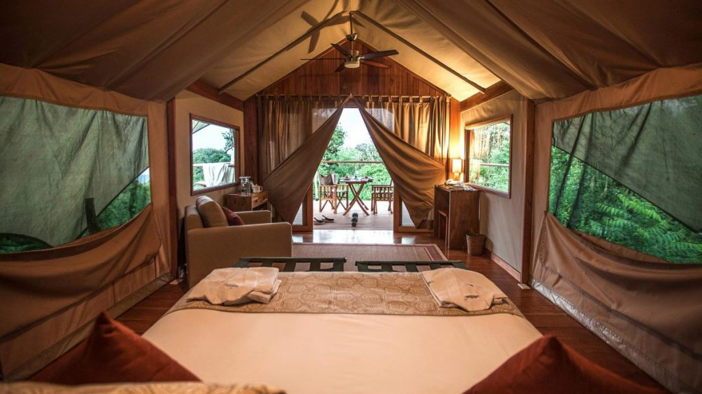 A queen sized bed with white linens and terracota colored pillows faces the luxury tent opening onto a private balcony with a small table and chairs. The room has a ceiling fan, large zipping windows, and comfy reading chair.