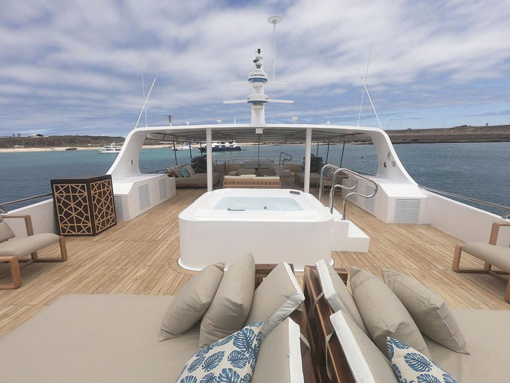 The Sea Star Journey cruise has a wooden sundeck with a covered sitting area, a jacuzzi in the middle, and beige lounge chairs in the open air.