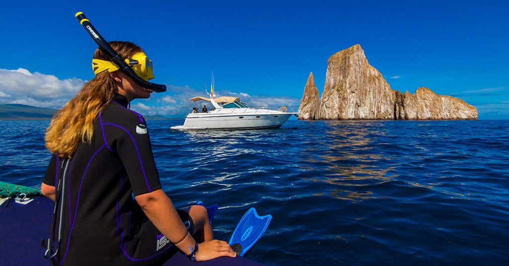 A snorkeler sits on the edge of a dinghy in front of Kicker Rock and a small yacht.