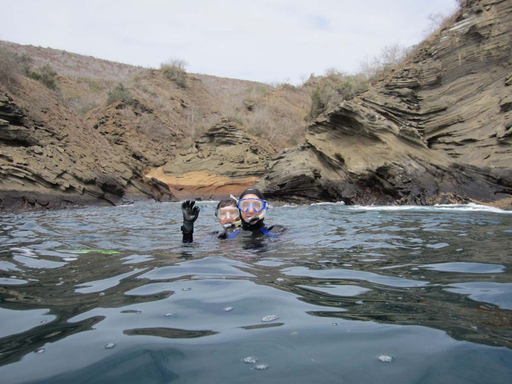 A pair of snorkelers give the OK sign in a rocky outlet of Isabela Island.