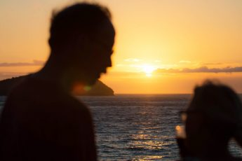 Silhouette of a couple honeymooning in the Galapagos looking at at a sunset over the ocean.
