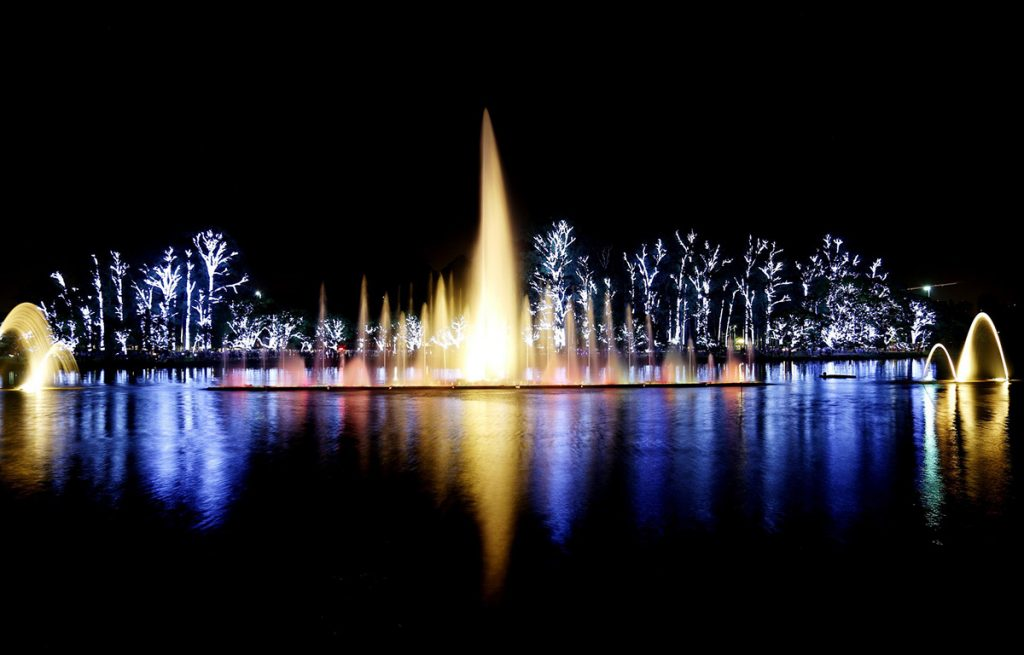The Ibirapuera Park in São Paulo lit up at night during the water show. The water glows with the reflection of the lights.