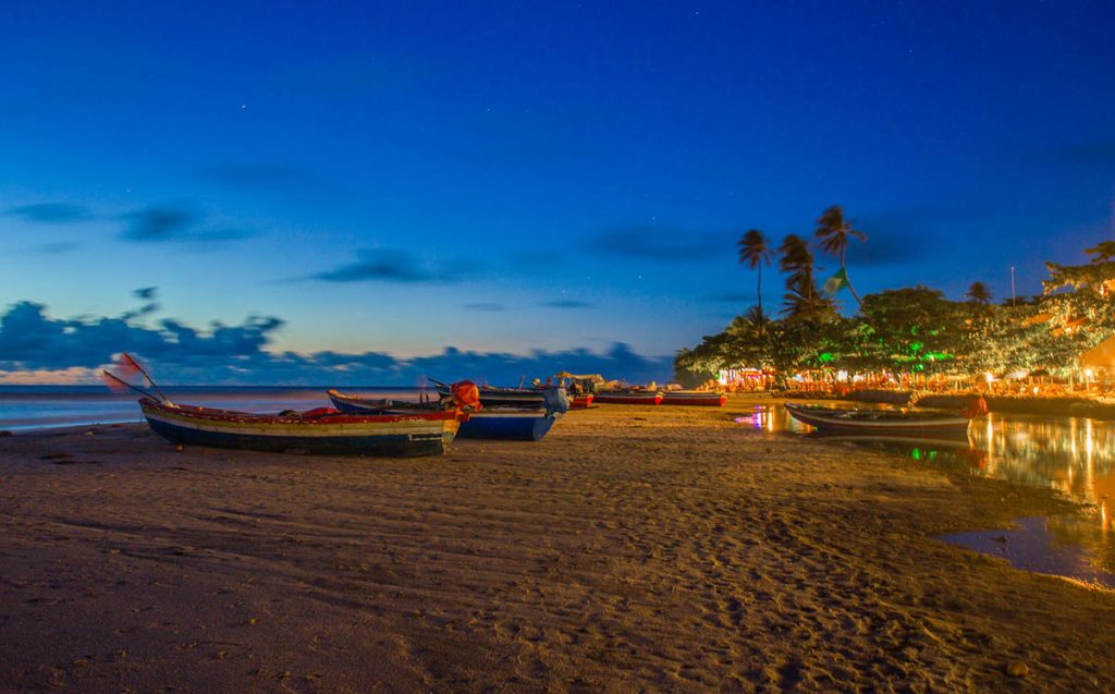 The lights of the town shine bright as the sun sets on the beaches of Jijoca de Jericoacoara in Brazil.