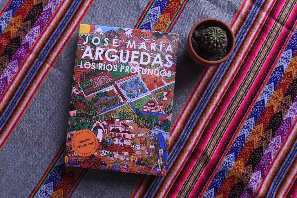 The centenarian edition of Deep Rivers in Spanish with colorful cover art depicting an Andean village. The book sits atop a woven Andean tablecloth next to a small cactus.