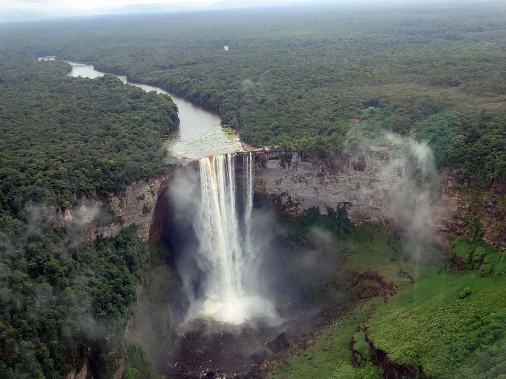 A birds-eye-view of the Kaieteur Falls cascading down into a canyon. The falls are surrounds by thick forest vegetation.
