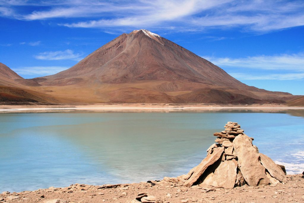 A towering mountain stands tall in the background. Laguna Verde is pictured in the foreground with vibrant blue-green colors.