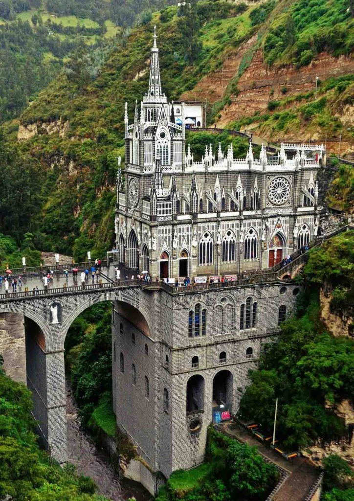 Tourists stand looking over the bridge to Las Lajas Sanctuary in Colombia. The church is situated on a canyon.