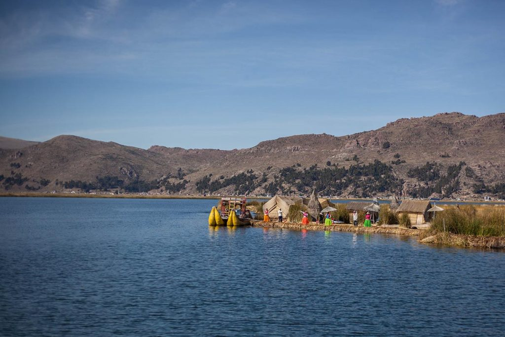 People dressed in brightly-colored traditional clothing welcome tourists to the Floating Islands on Lake Titicaca.