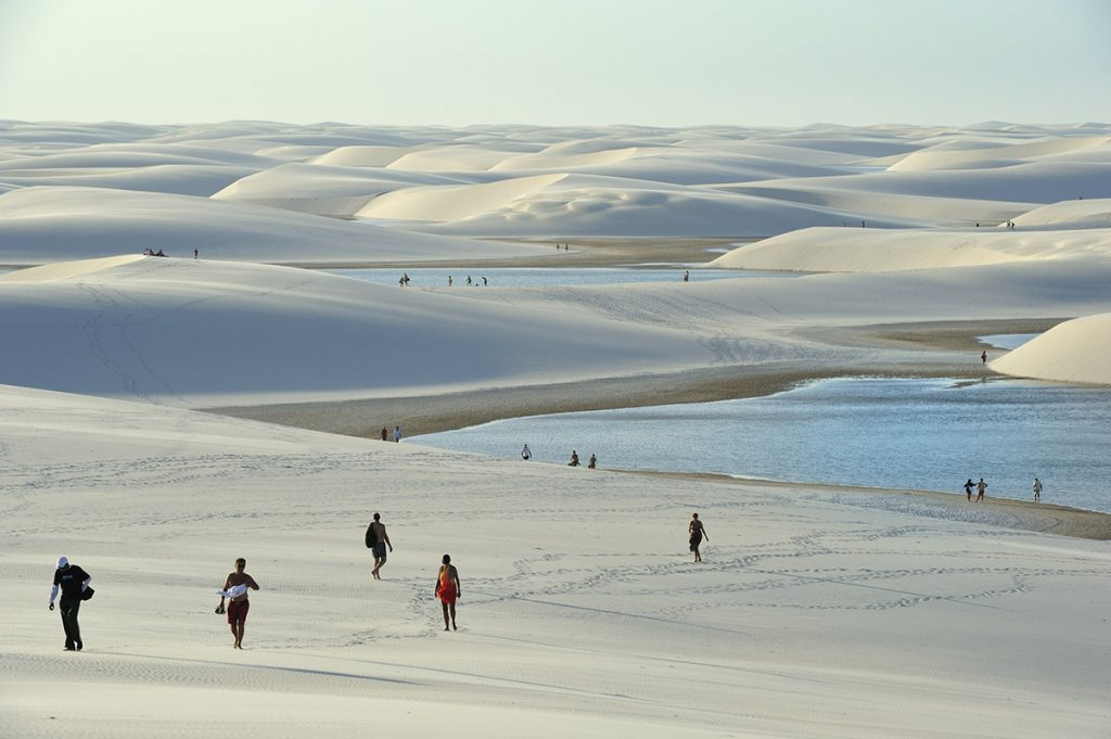Tourists are scattered across the sweeping sand dunes enjoying the views. The dunes are a pale tan/white color and bits of water can be seen.