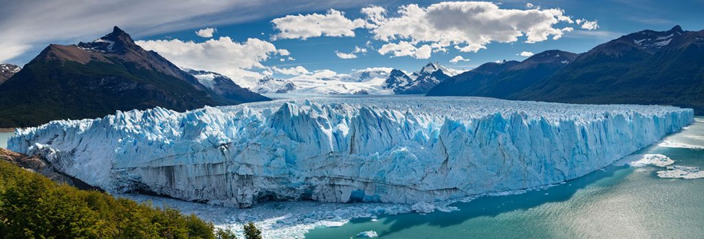 A panoramic view highlighting the massive white-blue glaciers of Los Glaciares National Park in Argentina.