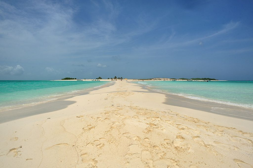 Looking across a sandbar that expands from Los Roques Islands in Venezuela. The sand is a perfect white and the waters are clear blue.