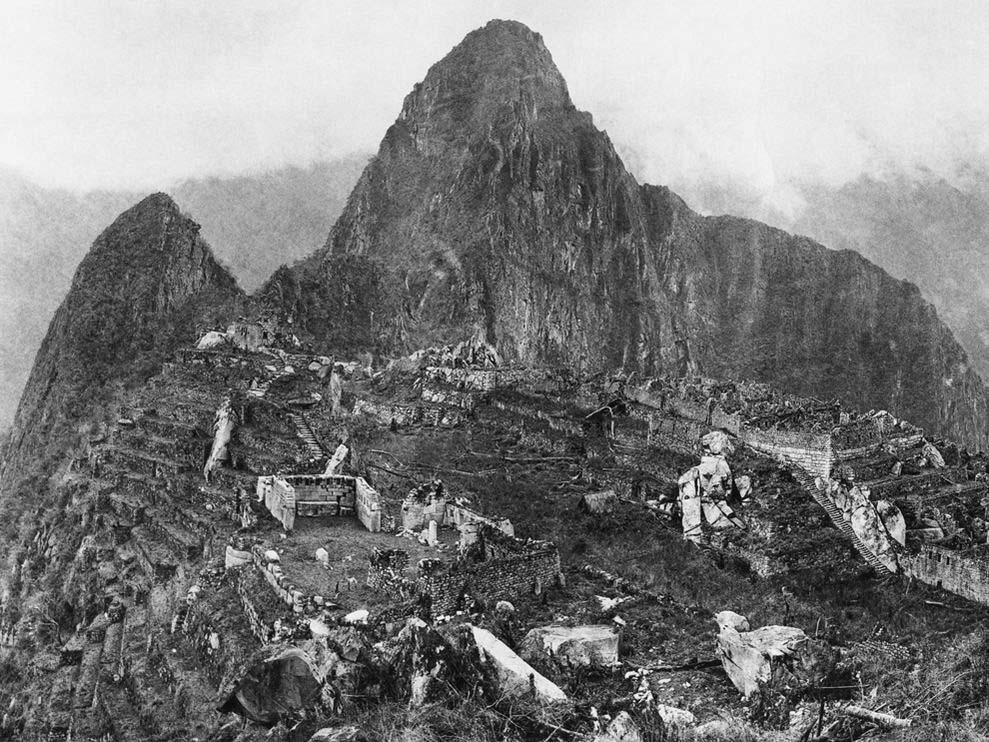 An old black and white photograph of Machu Picchu with Huayna Picchu behind after the site's discovery.