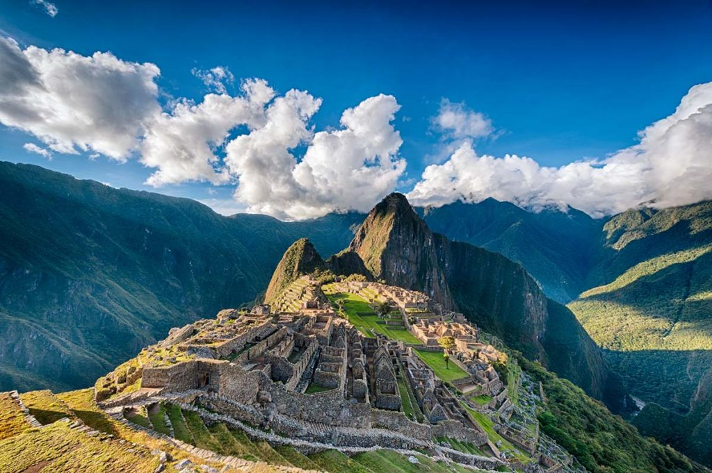 A super wide photograph of Machu Picchu and the surrounding mountains on a partly cloudy day. The ruins are lit up by the sun.