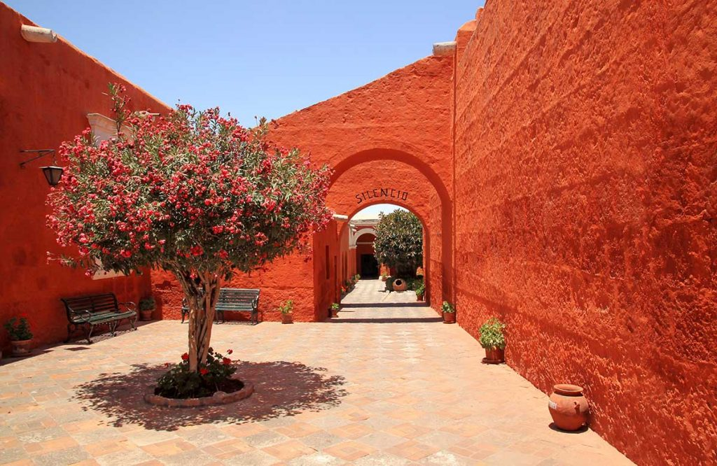 "A word, ""silencio,"" is written on one of the arches indicating to the visitor to be silent and reverent. The walls are bright orange-red and a tree blooms in the courtyard with flowers to match."