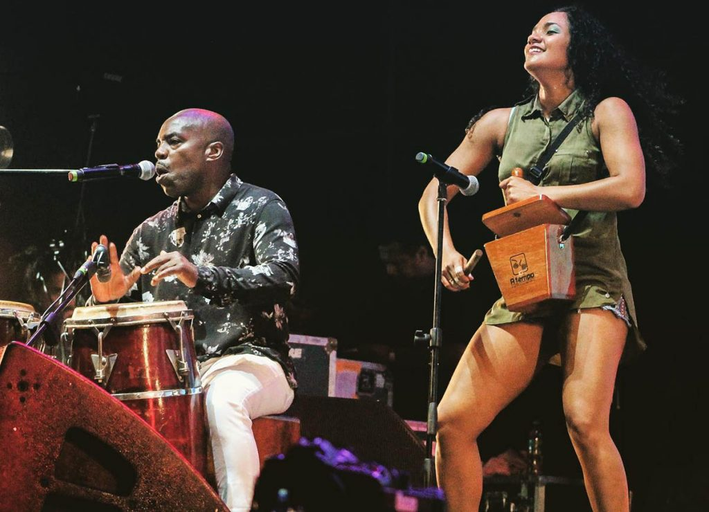 One member of the Afroperuvian musical group Novalima plays an African-styled drum while another plays a wooden percussion instrument with a baton.