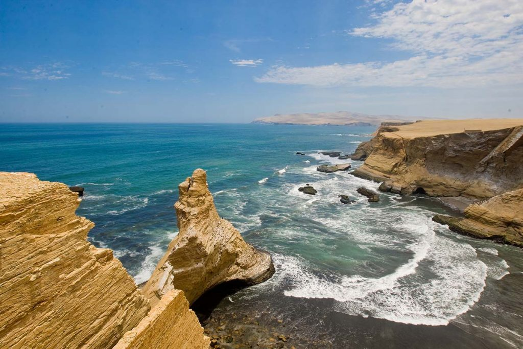 A bright and sunny day at the Paracas National Reserve. The sandy cliffs stand tall above the blue ocean waves.