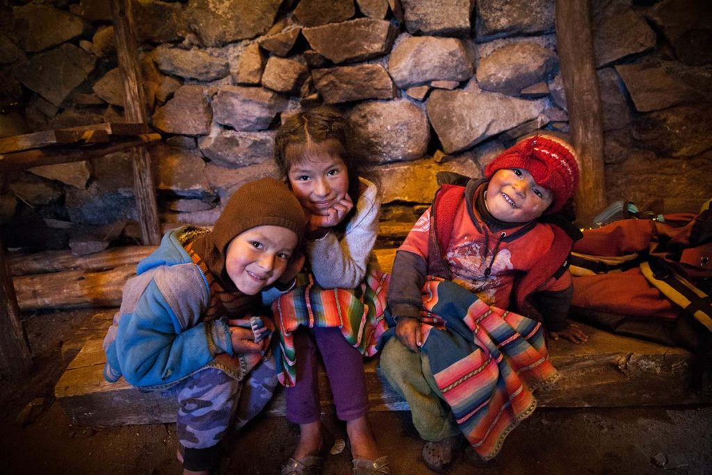 Three Andean children in sweatshirts, hats and covered in a blanket smile at the camera.