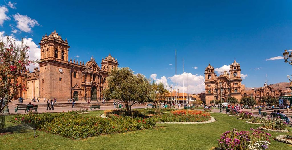 Two Spanish-style cathedrals frame the photo of the main Plaza de Armas in Cusco. The green park area is lined with flowers and people enjoy the sun.