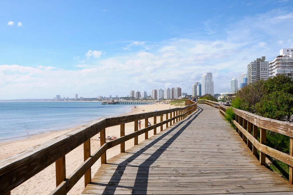 A view looking down the coast of Punta del Este from a boardwalk. You can see the hotels lining the beach.