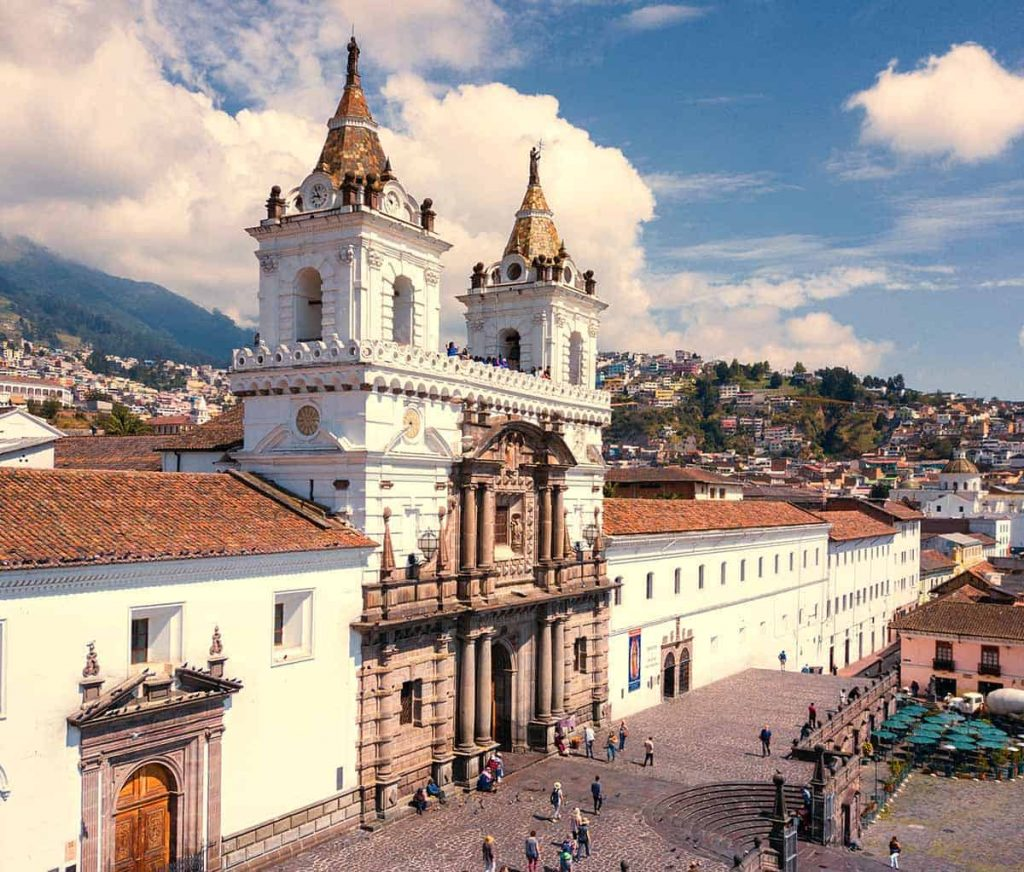 A view of the famous Iglesia de San Francisco, a bright white and brown church, in Quito, Ecuador.