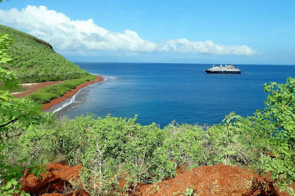 A view from red rocks and green shubery of Rabida Island of a Galapagos cruise ship in a bright blue bay.