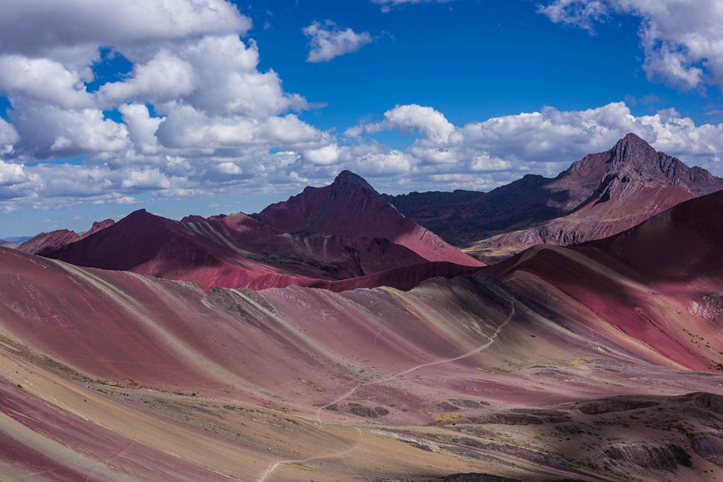 a path leading up rainbow mountain with blue skies and a few white clouds