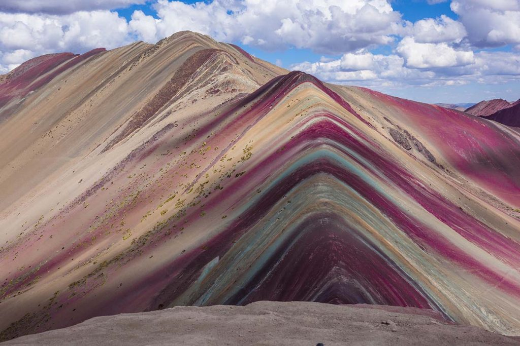A cloud passes over the Rainbow Mountain in Peru, casting a shadow on the colorful stripes.