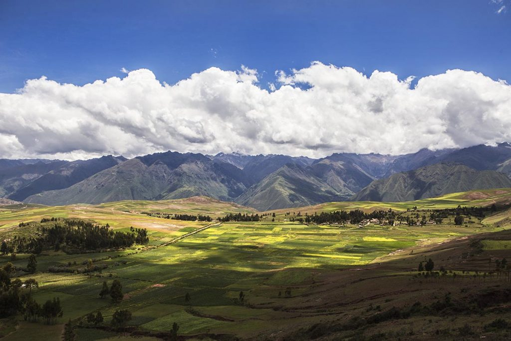 The sun shines between the clouds on the Sacred Valley of the Incas. The bright green landscape is half cast in shadow with the mountains rising in the background.