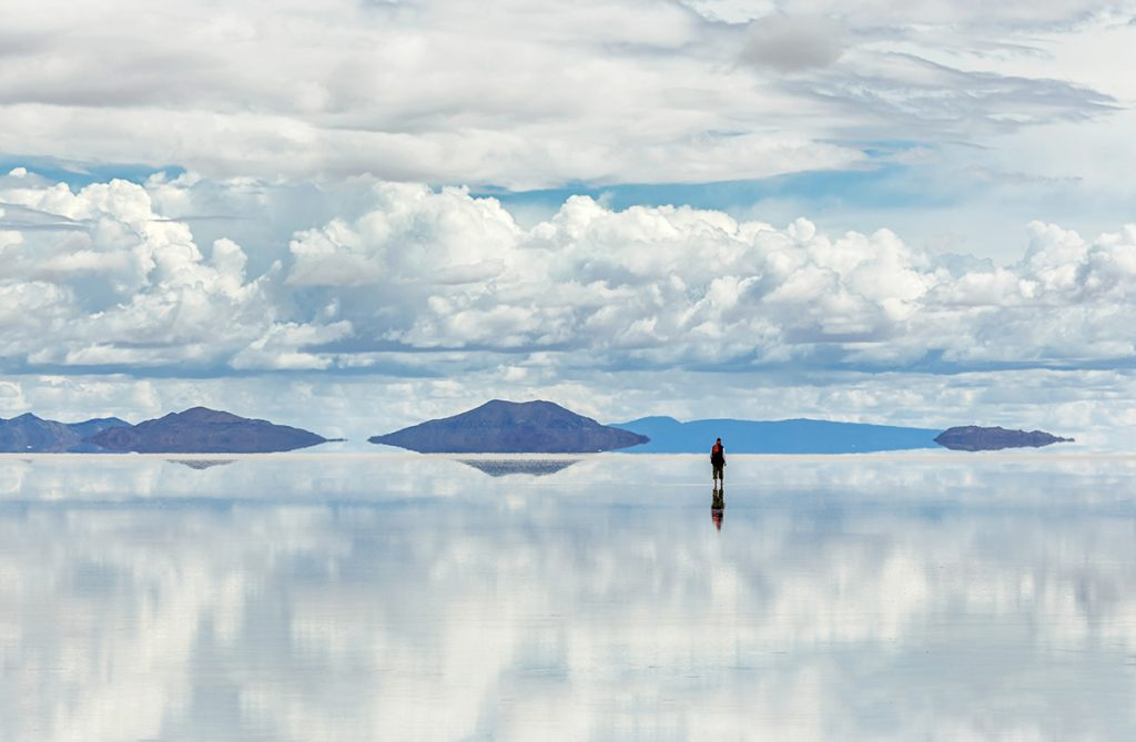 A man stands in the distance admiring the Bolivian salt flats of Salar de Uyuni. The clouds are mirrored in the reflection cast in the flats.