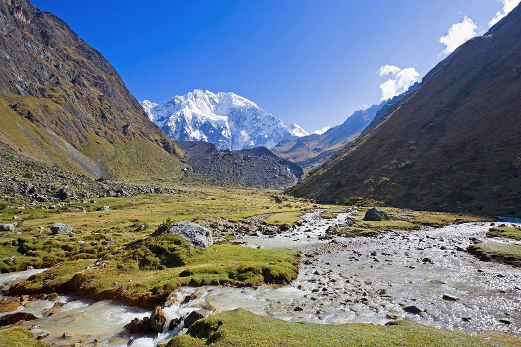 The snow-capped peak of Salkantay Mountain looms in the distance. The green valley, river and rocky terrain are pictured in the forefront.