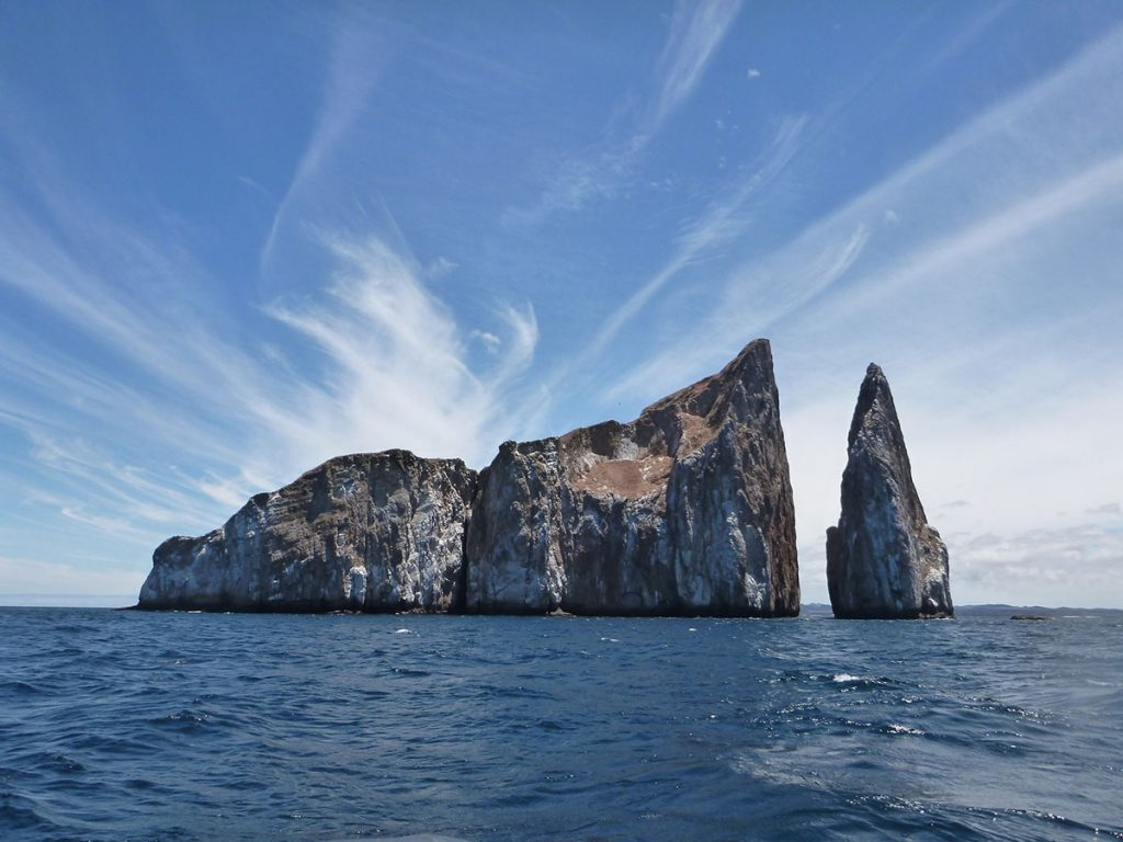 The unique rock formation Kicker Rock juts out of the ocean on a sunny day with white wispy clouds in the background.