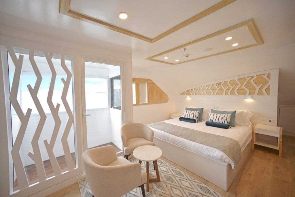 The Sea Star cruise's balcony suite includes a small balcony, sitting area, and large bed. The light decor includes light wood, white, grey, and beige.